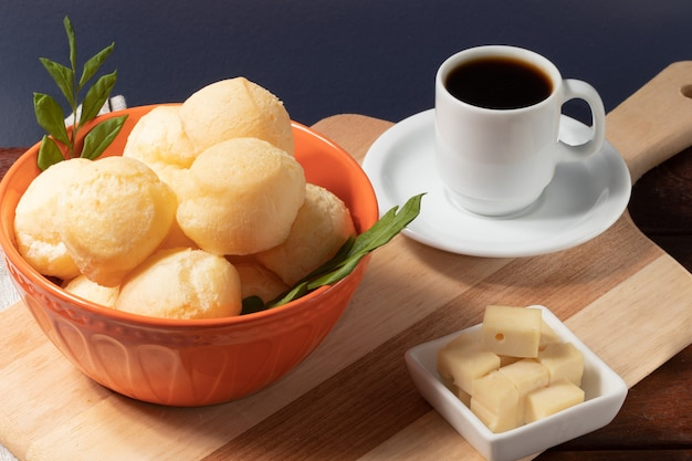 Pane al formaggio (pao de queijo) in una ciotola arancione e una tazza di caffè nero.