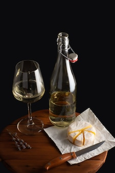Brie di formaggio e vino bianco serviti sulla tavola di legno marrone sopra la parete nera Foto Premium
