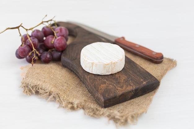Brie di formaggio con sulla tavola di legno rustica.