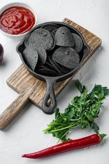 Set di snack croccanti al formaggio e erba cipollina, con salse per immersione salsa di pomodoro panna acida, in padella in ghisa, su superficie in pietra bianca