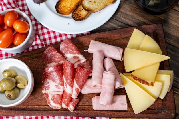 Tavola di formaggi e salumi, pomodorini, olive. vista a volo d'uccello.