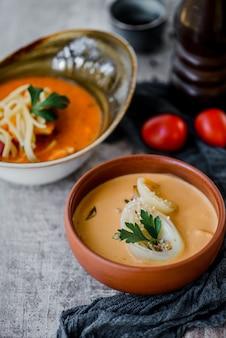 Zuppa di crema di formaggio e zuppa di pomodoro con verdure