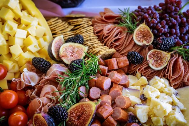 Formaggio, fichi, uva e cracker a bordo di salumi.