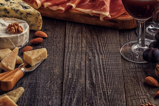 Formaggio, prosciutto, noci, uva e vino rosso su fondo di legno, fuoco selettivo, spazio della copia.