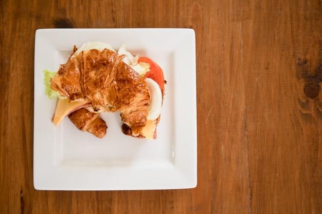 Croissant di prosciutto e formaggio servito sul tavolo.