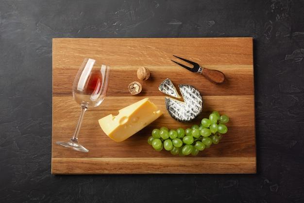 Testa di formaggio, grappolo d'uva, noci e bicchiere di vino sul tagliere a