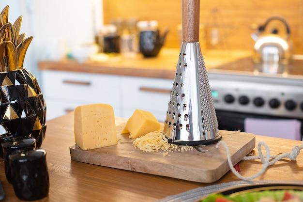 Il formaggio è sul tavolo vicino alla grattugia di ferro, immagine di una cena popolare