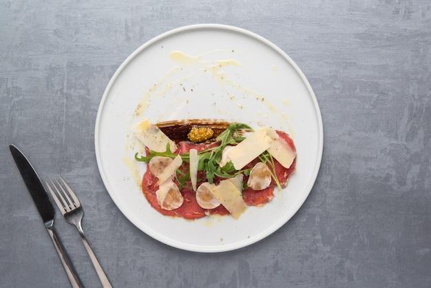 Formaggio e carne con verdure in un piatto su sfondo grigio