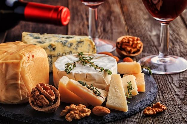Formaggio, noci, miele e vino rosso sulla superficie in legno