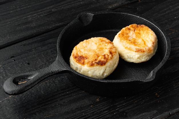 Frittelle di formaggio su padella padella in ghisa su padella padella in ghisa, su un vecchio tavolo di legno scuro sfondo