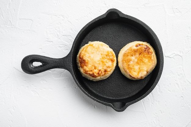 Frittelle di formaggio su padella in ghisa padella su padella in ghisa, vista dall'alto piatta, su pietra bianca tableta