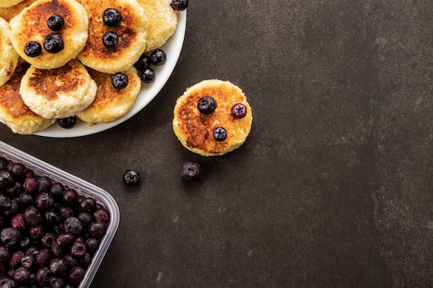 Frittelle di formaggio con mirtilli gelato, su uno sfondo scuro, vista dall'alto, sfondo scuro con texture con posto per il testo