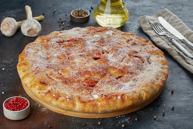 Torta di formaggio su piatto di legno rotondo con ingredienti intorno su superficie scura