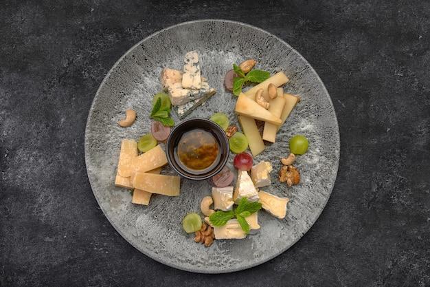 Piatto di formaggi, formaggi assortiti con menta, frutta candita, miele e biscotti, su un piatto