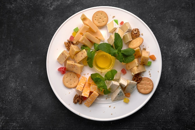 Piatto di formaggi, formaggi assortiti alla menta, frutta candita, miele e biscotti, su un piatto bianco, su uno sfondo scuro