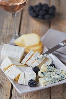 Piatto di formaggi. assortimento di formaggi con frutti di bosco e bicchiere di vino rosato su fondo di legno.