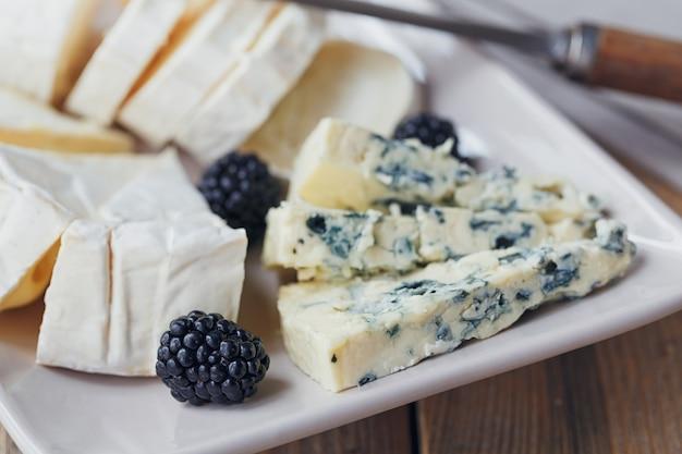 Piatto di formaggi. assortimento di formaggi con frutti di bosco su fondo di legno.
