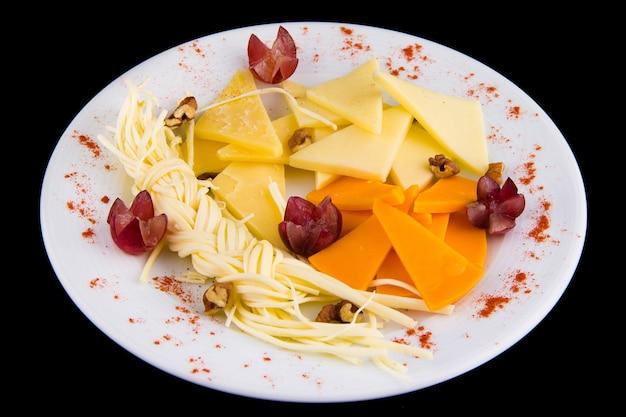 Piatto di formaggi - tagliere di salumi con vari tipi di formaggio a pasta dura e formaggio a pasta filata, decorato con uva, su piatto bianco isolato su sfondo nero vista dall'alto