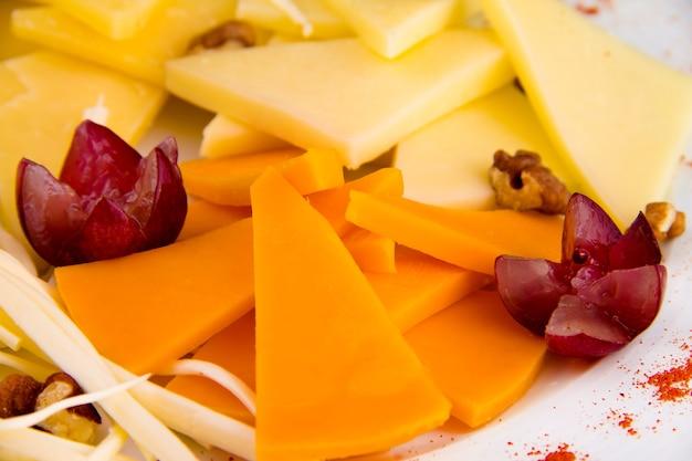 Piatto di formaggi - tagliere di salumi con vari tipi di formaggio a pasta dura e formaggio a pasta filata, decorato con uva, su piatto bianco isolato su sfondo nero