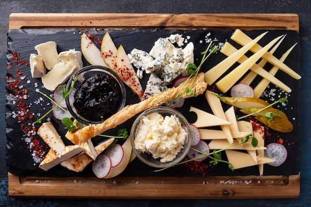 Piatto di formaggi servito marmellata e pera. vista dall'alto. avvicinamento