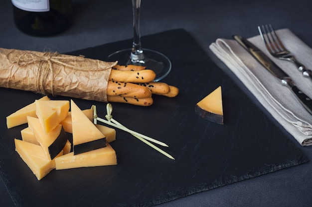 Piatto di formaggi servito con cracker e bicchiere di vino bianco su sfondo scuro. vecchio gouda su piatto da degustazione