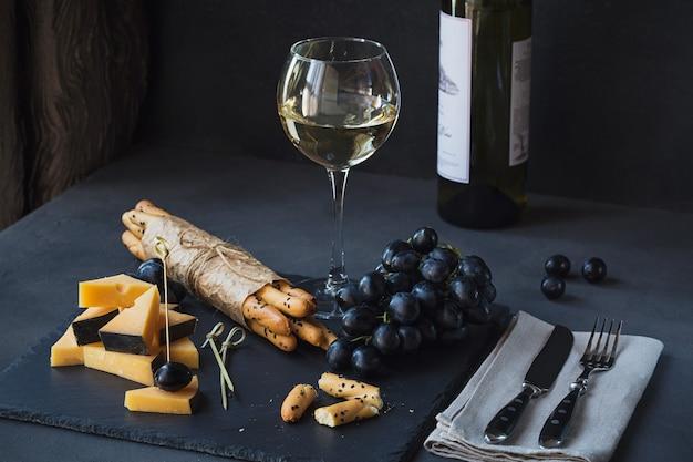 Piatto di formaggi servito con cracker, uva e bicchiere di vino bianco su sfondo scuro. vecchio gouda su piatto da degustazione