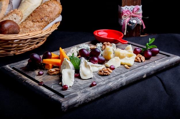 Piatto di formaggi servito con uva, miele e noci su uno sfondo di legno. vari tipi di formaggio