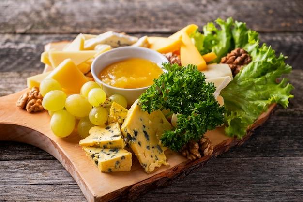 Piatto di formaggi servito con uva, noci e miele su un tavolo in legno primo piano