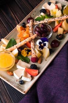 Piatto di formaggi servito con uva e noci.