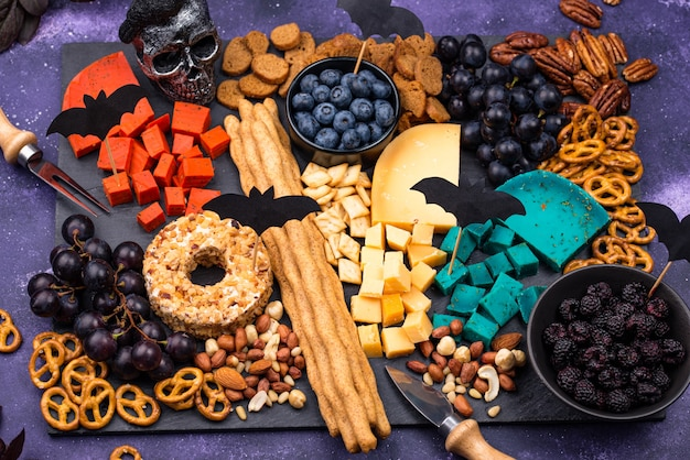 Piatto di formaggi con frutti di bosco, uva, noci e snack. cibo di halloween.