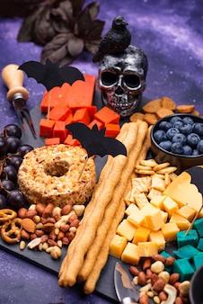 Piatto di formaggi con frutti di bosco, uva e snack