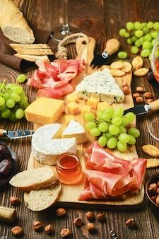 Piatto di formaggi con dorblu, brie, cheddar, prosciutto, uva, miele, datteri, cracker, noci e vino
