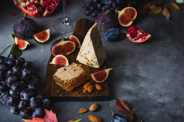 Piatto di formaggi con formaggio dorblu, uva, fichi, salse e vino rosso