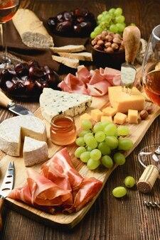 Piatto di formaggi con prosciutto, uva, miele, datteri, cracker, noci e vino