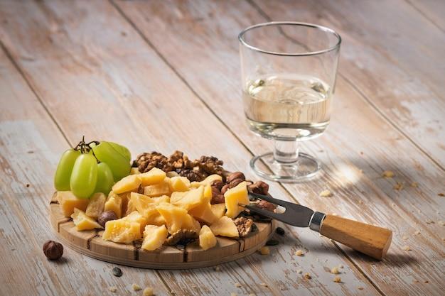 Piatto di formaggi con una varietà di snack su un tavolo di legno con un bicchiere di vino.