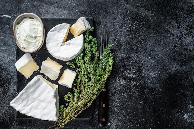 Piatto di formaggi. camembert, brie, gorgonzola e crema di gorgonzola al timo. sfondo nero. vista dall'alto. copia spazio.