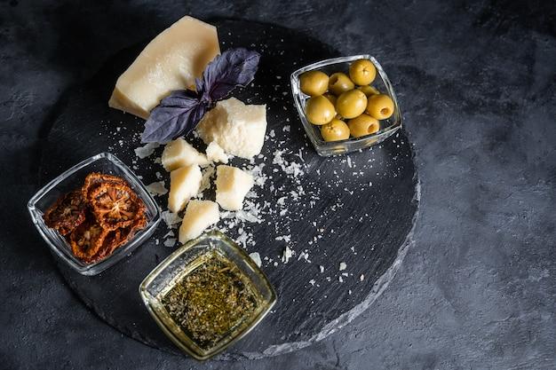 Piatto di formaggi servito su tavola di pietra.