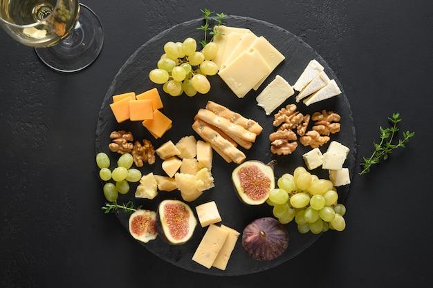 Piatto di formaggi con fichi di noci d'uva su sfondo di ardesia nera vista dall'alto