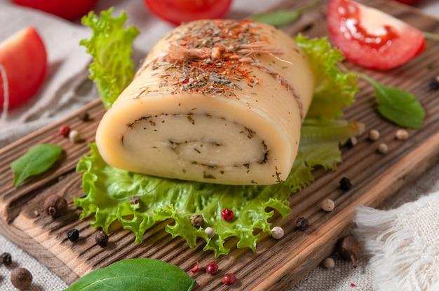 Rotolo di formaggio con erbe di oliva su un foglio di lattuga. su una tavola di legno. avvicinamento. decorate con rucola, spezie e pomodori. tessuto di lino grigio di sfondo. avvicinamento.