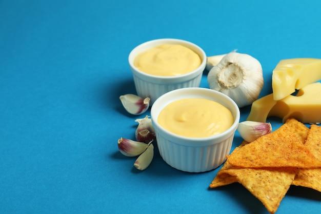 Salsa al formaggio, ingredienti e patatine su sfondo blu