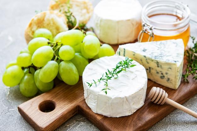 Selezione di formaggi, miele e uva sul tavolo di cemento grigio
