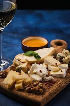 Set formaggio con miele e noci. assortimento di formaggi su una tavola di legno. set di antipasti di formaggio.