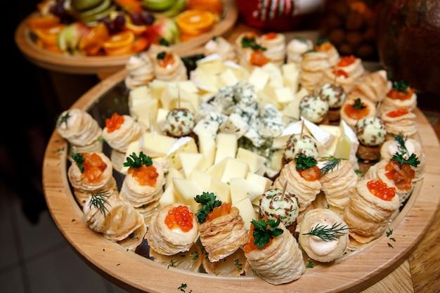 Snack al formaggio su un vassoio in legno.