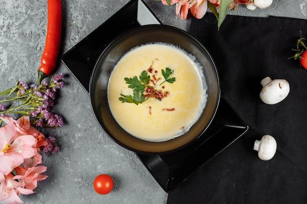 Zuppa di formaggio in una banda nera sulla tavola grigia.