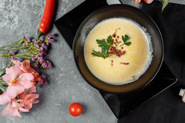Zuppa di formaggio in un piatto nero