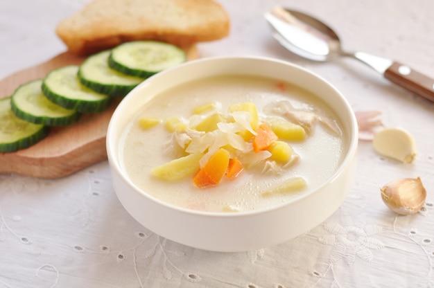 Zuppa di formaggio con pollo e verdure in ciotola bianca, cetriolo e aglio in un tovagliolo di tessuto. messa a fuoco selettiva