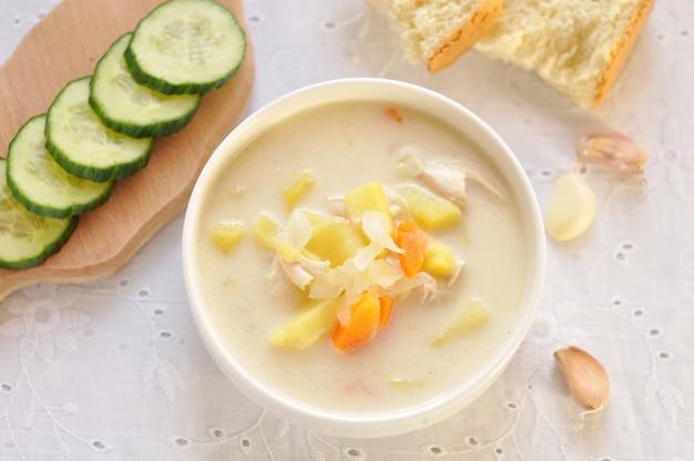 Zuppa di formaggio con pollo e verdure in ciotola bianca, cetriolo e aglio in un tovagliolo di tessuto. vista dall'alto