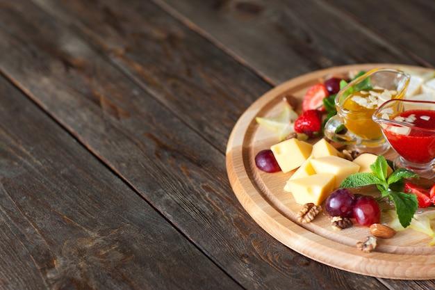 Formaggio con uva e salse su tavola di legno