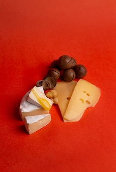 Formaggio con noci e miele su fondo rosso