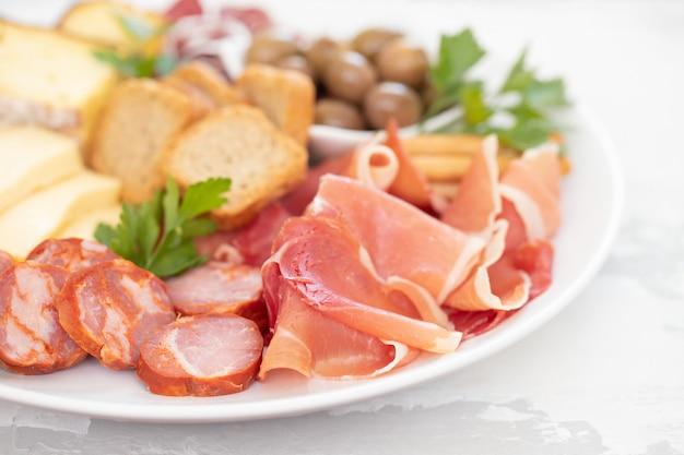 Formaggio con carne affumicata sul piatto bianco